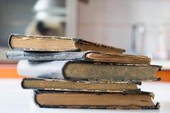 Gamla böcker som staplas på en vit tabell Gammal frigörare utan titlar Royaltyfri Fotografi