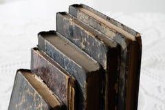 Gamla böcker som staplas på en vit tabell Gammal frigörare utan titlar Arkivfoton