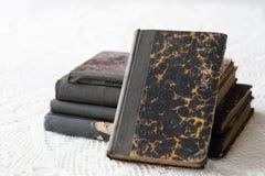 Gamla böcker som staplas på en vit tabell Gammal frigörare utan titlar Arkivbilder