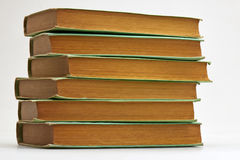 Gamla böcker som staplas på vit bakgrund arkivbilder