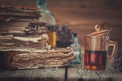 Gamla böcker, tinktur eller sunt te i exponeringsglas, liten medicinflaska av homeopatiska små kulor och medicinska örter Royaltyfria Bilder