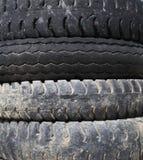Gamla bilgummihjul vid texturbakgrund Royaltyfri Fotografi