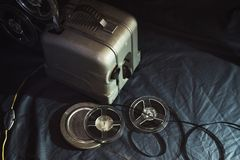 Gamla bioprojektor och kassetter i mörkret arkivfoton