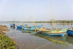 Gamla blåa stora fiskebåtar med motorer och metspön som ankras av kusten mot bakgrunden av en flod och gröna träd royaltyfri fotografi