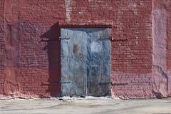 Gamla blått målad industriell dörr på väggen för röd tegelsten royaltyfri bild