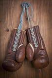 Gamla boxninghandskar med en snöra åt över träväggen Royaltyfria Foton