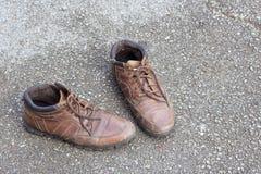 Gamla bruna läderskor på cementgolv Arkivfoton