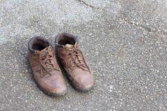 Gamla bruna läderskor på cementgolv Arkivfoto