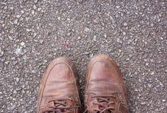 Gamla bruna läderskor på cementgolv Arkivbilder