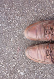 Gamla bruna läderskor på cementgolv Royaltyfri Fotografi