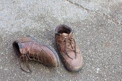 Gamla bruna läderskor på golvet Arkivbild