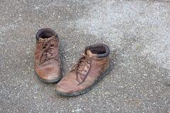 Gamla bruna läderskor på golvet Arkivfoton