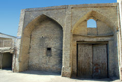 Gamla Bukhara bågar av vit tegelsten med träporten Royaltyfria Foton