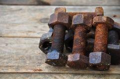 Gamla bultar eller smutsar ner bultar på träbakgrund, maskinutrustning i branscharbete Arkivbild