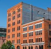 Gamla byggnader för röd tegelsten med blåa Windows under klar himmel Fotografering för Bildbyråer