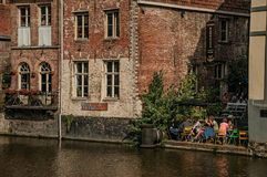Gamla byggnader framme av kanalen och folket i Ghent Fotografering för Bildbyråer