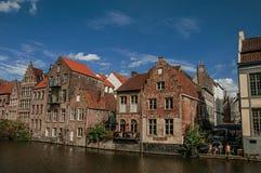Gamla byggnader framme av kanalen och folket i Ghent Royaltyfria Foton