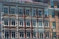Gamla byggnader som reflekterar i fönstren av en andra byggnader i t Royaltyfri Bild