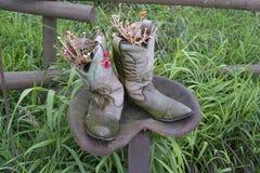 Gamla cowboykängor med blommor på traktorplats Royaltyfri Fotografi