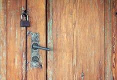 Gamla dörrar med det rostiga den dörrhandtaget och hänglåset arkivfoto