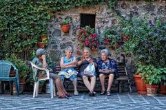 Gamla damer som samlar i den huvudsakliga fyrkanten i Radicofani, Tuscany arkivbild