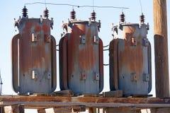 Gamla elektriska transformatorer på en trästruktur arkivfoton