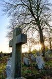 Gamla engelska gravstenar som ses under solnedgång i mitt- vinter i en engelsk kyrkogård arkivbild
