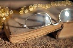 Gamla exponeringsglas som ligger på en tappningbok med en suddig bakgrund och en härlig bokeh arkivbild