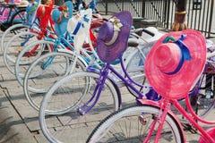 Gamla färgglade cyklar för Retro design med kvinnahattar och hjälmar Arkivbild