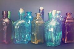 Gamla färgglade flaskor mot en mörk bakgrund Arkivfoto