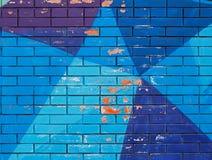 Gamla färgrika blått målar med sprickor på tegelstenväggen arkivfoton