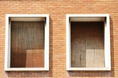 Gamla fönster med wood paneler som behöver en renovering på ett tegelstenhus Royaltyfri Foto