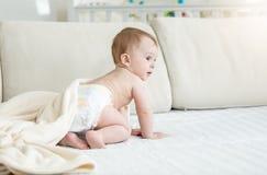 Gamla förtjusande 10 månader behandla som ett barn pojken i blöjor som sitter på soffan Royaltyfri Foto