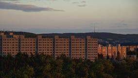Gamla fabrikstillverkade delarna till bostadsområden på solnedgången Arkivbild