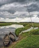 Gamla fartyg på banken av en liten flod Arkivbild