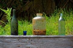 Gamla flaskor och krus kasserade på ett träträdgårds- staket royaltyfri foto
