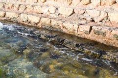 Gamla forntida gula stenmoment som täckas med grön gyttja och gyttja, nedstigning in i havet, sjö, hav och vatten med vågor Backg royaltyfria bilder