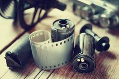 Gamla fotofilmrullar, kassett och retro kamera arkivfoton