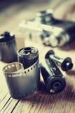 Gamla fotofilmrullar, kassett och retro kamera Royaltyfri Foto