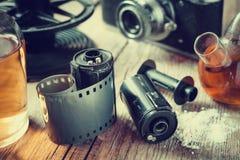Gamla fotofilmrullar, kassett, retro kamera och kemikaliereagen royaltyfria foton