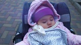Gamla fridsamma 8 månader behandla som ett barn flickan som sover i en sittvagn som är utomhus- på ett kallt väder - slags tvåsit stock video