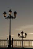Gamla gatalampor och räcke på en bro, Backlit av Dawninen Arkivfoton