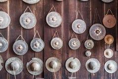 Gamla Gongs och kanstött cymbal på den Wood väggen Arkivfoton