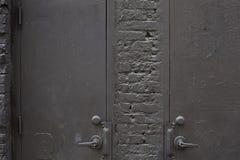 Gamla grå färger belägger med metall dörrar och bakgrund för tegelstenvägg Arkivbild
