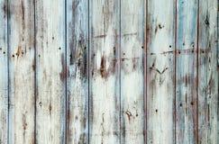 Gamla grungy och red ut vita grå färger och den blått målade träväggplankan texturerar bakgrund som ridas ut av lång exponering Arkivbild