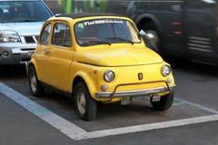 Gamla gula Fiat 500 som parkeras på gatan i Rome, Italien Royaltyfri Bild