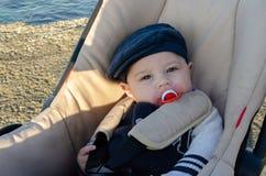 Gamla gulliga 4 månader behandla som ett barn pojken som sitter i pushchairen på stranden med den blåa hatten och den röda fredsm royaltyfria bilder