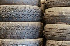 Gamla gummihjul för använd bil som staplas upp i lagringsområdet arkivbilder