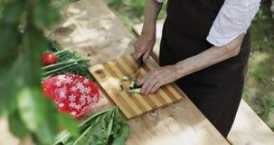 Gamla händer för farmor` s gör en ny sallad av grönsaker lager videofilmer