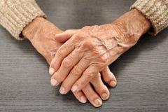 Gamla händer med artritis Arkivfoto
